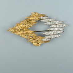 A diamond brooch, by Andrew GRIMA,  of openwork abstract design, the lozenge shaped plaque composed of 8 old brilliant-cut diamond tapering torpedo segments arranged in horizontal formation, with abstract textured detailing (hva)