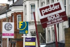 © Reuters. Estate agents boards are lined up outside houses in south London