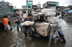 Filipino workers load goods on a tricycle along a flooded area in suburban Navotas, north of Manila, Philippines. ■ Photo: AP