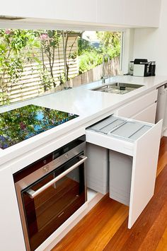 Kitchen Design Idea - Hide Pull Out Trash Bins In Your Cabinetry | These trash bins hang from the top of the drawer making them slightly closer to you and even more convenient to use.