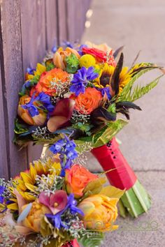 Lovely bright and colorful Bridal bouquet using tangerine tango roses, delphinium, sunflowers, and billy balls