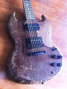 This is a little SG inspired killer has a hand cut/carved walnut body and a bolt-on maple neck. The body looks like a big piece of chocolate! The pickups here are a P90 sounding humbuckers but have since been replaced with Gibson Classic '57s. Now it sounds like a monster! Pick guard, control cover and truss rod cover are mahogany as well. All hardware is black chrome.