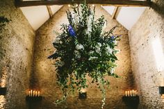 Large blue, white & red hanging floral arrangement from the beams of a barn - Image by Samuel Docker Photography - Claire Pettibone lace dress in a rustic barn wedding in the Cotswolds with red bridesmaid dresses. Groom wears a Reiss Suit with floral bow tie and light up letters decoration.