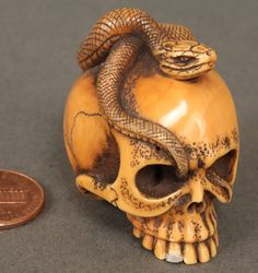 ba128b23d566 Japanese ivory netsuke of a skull with one silver tipped tooth and snake  perched on top with its tail tip resting in the skull socket.