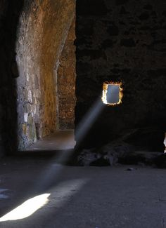 A shaft of sunlight streams through a window into the cellars and bakehouse in Dirleton Castle, Scotland.