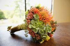 Succulent bouquet including pincushion protea, celosia, seeded eucalyptus, spray rose, green mini hydrangea and cymbidiums