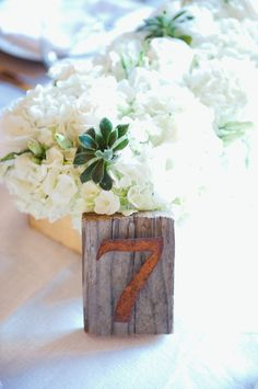 who will not love this wedding centerpieces idea using a table number, flower vase and beautiful flowers?