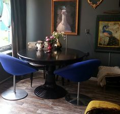 Blue chairs, black table, dark walls, eclectic artwork