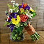 Iris, mums, daisies, ranunculus, carnations, tulips, and yellow solidago in bright spring colors create a beautiful rustic chic bouquet.  Flowers by A Floral Affair - www.afloralaffair.com #pdxweddings #weddingbouquet