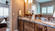 This bathroom has a his and hers countertop accompanied by dark stained cabinets.