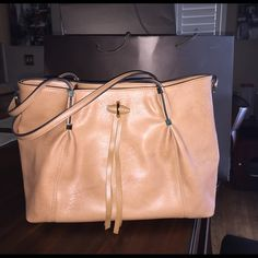 Beautiful large,  camel colored tote This is a used large camel colored, faux leather tote with lots of  room for everything you need to carry. Comes with two pockets on one side for cell phone, middle zipper area. Gold accent hardware. This bag looks brand new! Bags Totes
