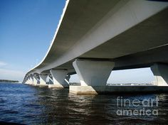 Florida Keys, USA -- View of Florida's Overeseas Highway from water level. See pileons holding up the bridge and curving lines of the highway. The Overseas Highway connects Florida Keys and ends at Key West.