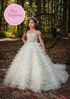 The Veracruz Flower Girl Dress For Wedding by MB Boutique Canada. An absolutely stunning Veracruz flower girl dress features a full-ruffled tulle floor-length skirt and gold embroidered lace overlay illusion bodice. The back of the dress grabs your attention with open neckline corset lacing, and an elegant train that extends from the hemline of the dress for the incredible looking appearance. The dress is presented by high-quality fabrics, thick and full bridal tulle at the bottom.