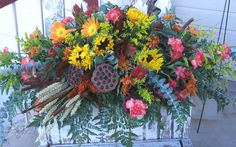 Eucalyptus, wheat, sunflowers, gerberas... I love the pods and the yellow filler (coleus?). Just not a fan of the carnations and their random pink