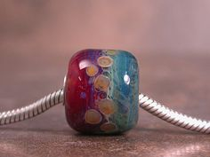 This is a chunky OOAK handmade big hole bead done in borosilicate glass. You will find shades of amber purples, watery blues, greens and