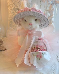 Heirloom Bunny created by Jennifer Hayslip - Ms. Bunny carries her basket of flowers lined with a vintage hankie. The basket is adorned with lace trim & vintage pearl earbob. The bunny's straw hat is embellished with pink paper roses.