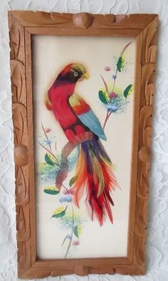 This vintage Mexican feather painting portrays a beautiful multi colored bird with a long tail. The background has painted flowers. It is framed and