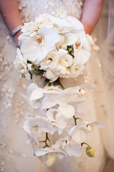 Cascading orchids and ranunculus. This is what I HAVE ALWAYS WANTED!!! I want orchids for my wedding and this is exactly what i was thinking too!!! AHHHH such a beautiful arrangement