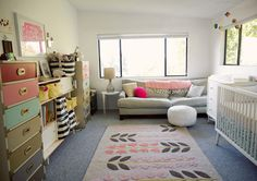 LOVE this little girl's room. Colorful campaign dressers, comfy couch, love the rug choices too! And open baskets for storage on the shelf. One neat thing here is that the walls and rug have barely been touched at all.