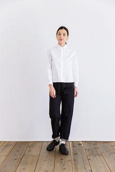 """YAECAの定番のコットンシャツ。身幅が広めのスクエアシルエットで、丈は短め。着ると、裾が軽く浮くように見えます。ホワイトは20%リネンを混紡したコットン素材で、少々分厚くしっかり目の手触り。バランスよく見せるには、ボトムはワイドシルエットのパンツや長め、あるいはある程度ボリュームのあるスカートが良さそうです。シャツの脇の裾部分が曲線状になっており、サイドシルエットのかわいらしさもポイントです。YAECAブランド名の由来は""""八重日""""という造語。「日々重ねて着てほしい」という願いが込められています。無駄をそぎ落としたシンプルなデザインは、「必然的に」編み出されたもの。着る人のくらしの中に溶け込み、その人を最も輝かせるために、ていねいに作られています。"""