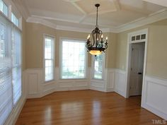 Dining room with bay window, wainscoting, and custom ceiling treatment.