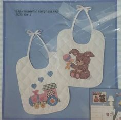 "Adorable, set of two, stamped cross stitch baby bibs, by Bucilla, #40354. Kit is brand new, never opened, titled: ""baby bunny n' toys"" size 10"" x 12""  bibs are white cotton blend, pre-quilted & pre-bound. Plastic wrapping on front of kit has been taped but never opened. Would make a darling shower gift or for your little one♡"
