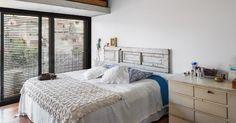 """No segundo pavimento, o dormitório é igualmente repleto de luz natural, somente quebrada pela porta veneziana, feita de madeira. Destaque para a cabeceira da cama, """"improvisada"""" com o uso de uma porta antiga de demolição. A decoração do apê da Vila Aspicuelta é dos arquitetos Rafael Loschiavo e Vera Molina"""