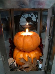 pumpkins made by cutting out hole for tea light and stacked inside lantern