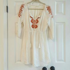 Solitaire Bohemian Vneck Dress .dress has a burnt orange embroidered design down the front and on both shoulders    (See picture 4 ). Almost like a quilting stitch around the neck. Has a drawstring closure in the front. Dress is fully lined but no tag with fabric information.  Dress is been gently washed and worn but is in great condition.  Dress has elastic at the waist. solitaire Dresses Mini