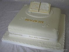 Square communion cake all finished in white with sugar made rosary beads and cross on the board and topped with a sugar made open book trimmed in gold and finished with scrolls and flowers and communion satin ribbon