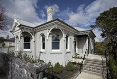 Originally a weatherboard villa, this house now features stone cladding and stone window and door reveals. The facelift also introduced new arched doorways and windows that are shuttered for privacy. Edwardian House, Victorian Homes, Arch Doorway, Stone Cladding, Contemporary Interior, Colonial, New Zealand, Facade, Villa
