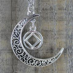"Narcotics Anonymous charm surrounded by a delicate antiqued silver filagree moon. The moon is 38mm x 35mm. The moon hangs from a 24"" stainless steel rope chain with clasp. Our higher power is like the"