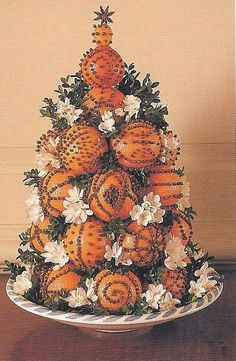 A dramatic cone designed with  clove-studded naval oranges  topped with a kumquat  is not only beautiful but smells wonderful!  Narcissus blooms are tucked in between along with boxwood as fillers.../click for more ideas