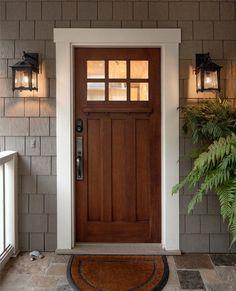 Craftsmen wood front door | Double sconces | Fern planter | Welcome mat | Gray siding |