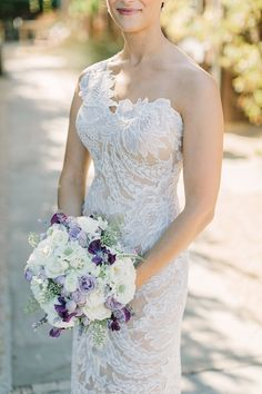 One shoulder lace Anna Maier Ulla-Maija wedding gown and a purple and white wedding bouquet @weddingchicks