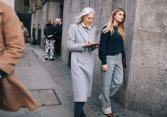 Ruth Chapman and Megan Reynolds, gray hair, overcoat, sweater, striped pants.