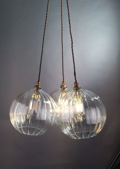 Hereford ribbed glass globe pendant light displayed in a pendant cluster chandelier.