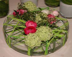 Glazen schaal met groene raffia, ranunkels, viburnum, en jasmijn