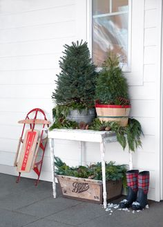 Put down the tinsel. Sometimes evergreens look best au naturel, especially when stationed outdoors on a porch or patio. These patio evergreens were placed in a galvanized tub and an orchard basket, while clippings and pinecones were arranged on the table and in the old crate below.