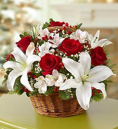Inspired by the stylish holiday bouquets found in bustling European flower markets this time of year, our florists designed this gathering of red roses, white lilies, alstroemeria and Christmas greens inside a classic handled basket. Perfect as a holiday centerpiece, hostess gift or for your own décor—no passport necessary.