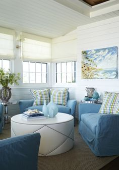Beachy living room with white tongue & groove walls & ceiling, coastal art canvas.