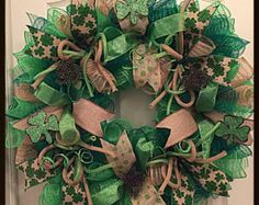 Celebrate the month of March with this St Patricks Day Deco Mesh Wreath-  It is made with high quality green, lime and white metallic deco mesh-  There are numerous ribbons in glittered green, lime and silky white.  Lime flex tubing and glittered spring picks have been placed all around the wreath.  There is a large double shamrock in the middle of the wreath. It has been handcrafted out of wood, painted and glittered green and lime and shows with raffia and a green bow.  This wreath…