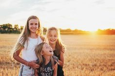 Portrait of 3 sisters in french cornfield at sunset UK Essex child photographer