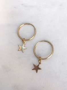 Stay on trend with these minimalistic hoop earrings! These gold filled hoops measure 16mm with a 8mm star dangling from the bottom. Choose from gold-filled hoops or sterling silver.