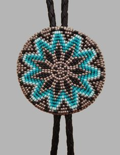 Native American made beaded Bolo tie in turquoise, black and metallic gray seed beads. The tie measures 1 and 7/8 inch in diameter. The slide