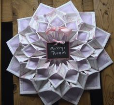 19 foldn stitch wreath. Done in light purple and pink fabric. This is accented with a small chalk board 3x4 . You can personalized to what ever you would like it to say. This would ok very nice on a little girls door with her name written on the chalk board.