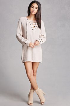 39a70d55977d A marled knit sweater dress featuring a lace-up with grommets on the front  and