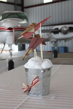 paper airplane center pieces - instead of buckets, I think it would be even cuter maybe to put bunches of cotton here and there (with the airplanes in them as in the pic) on a sky blue table cloth.