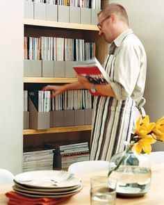 To neatly house an extensive collection of magazines, this kitchen has a wall of custom cabinets. The deep shelvescontain double rows of issues.