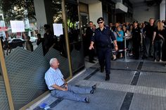 Retiree Giorgos Chatzifotiadis had queued up at three banks in Greece's second city of Thessaloniki hoping to withdrawing a pension on behalf of his wife, but all in vain. When he was told at the fourth that he could not withdraw his 120 euros, he collapsed in tears. (Sakis Mitrolidis/AFP/Getty Images)